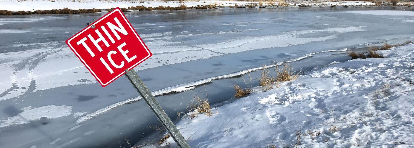 A frozen water way with a red sign, leaning, that says thin ice.