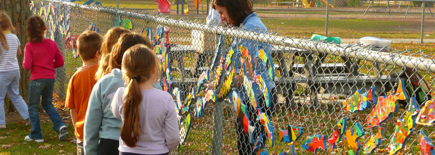School children walk along a chain link fence with a recently installed stream of dreams mural, painted wooden fish cutouts fixed to the fence in an art mural..