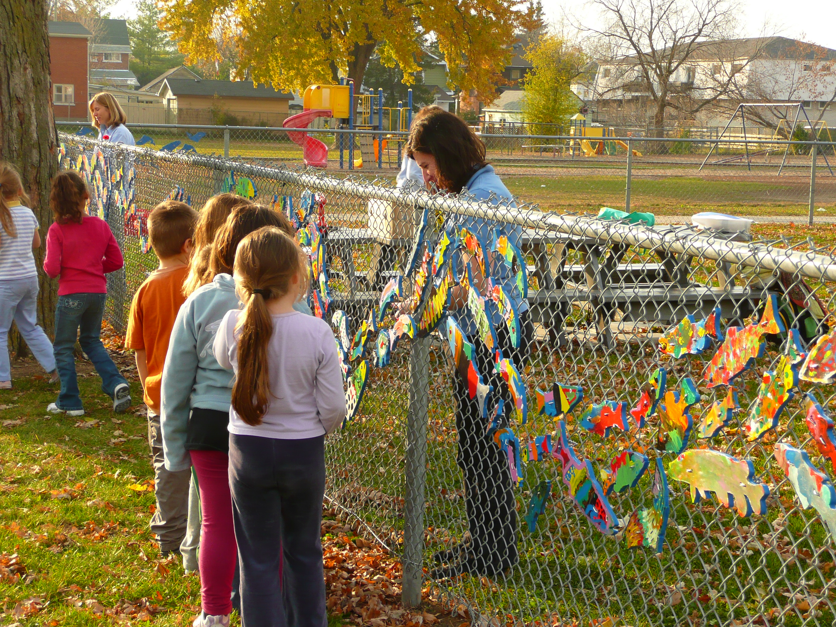Children looking at painted fish on a fence infront of a school