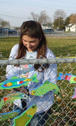 The dream fish are being installed on a chain link fence in front of a school.