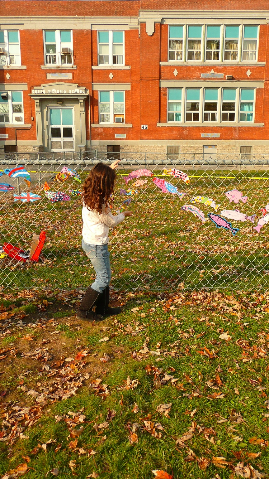 a young girl walks along a chain link fence where painted wooden fish create an art mural called a Stream of Dreams