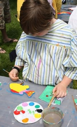 child, standing at a table, paints a wooden fish cutout with a variety of colours as their dream fish