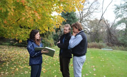 3 Staff members standing in open grassy area and reviewing information in binder