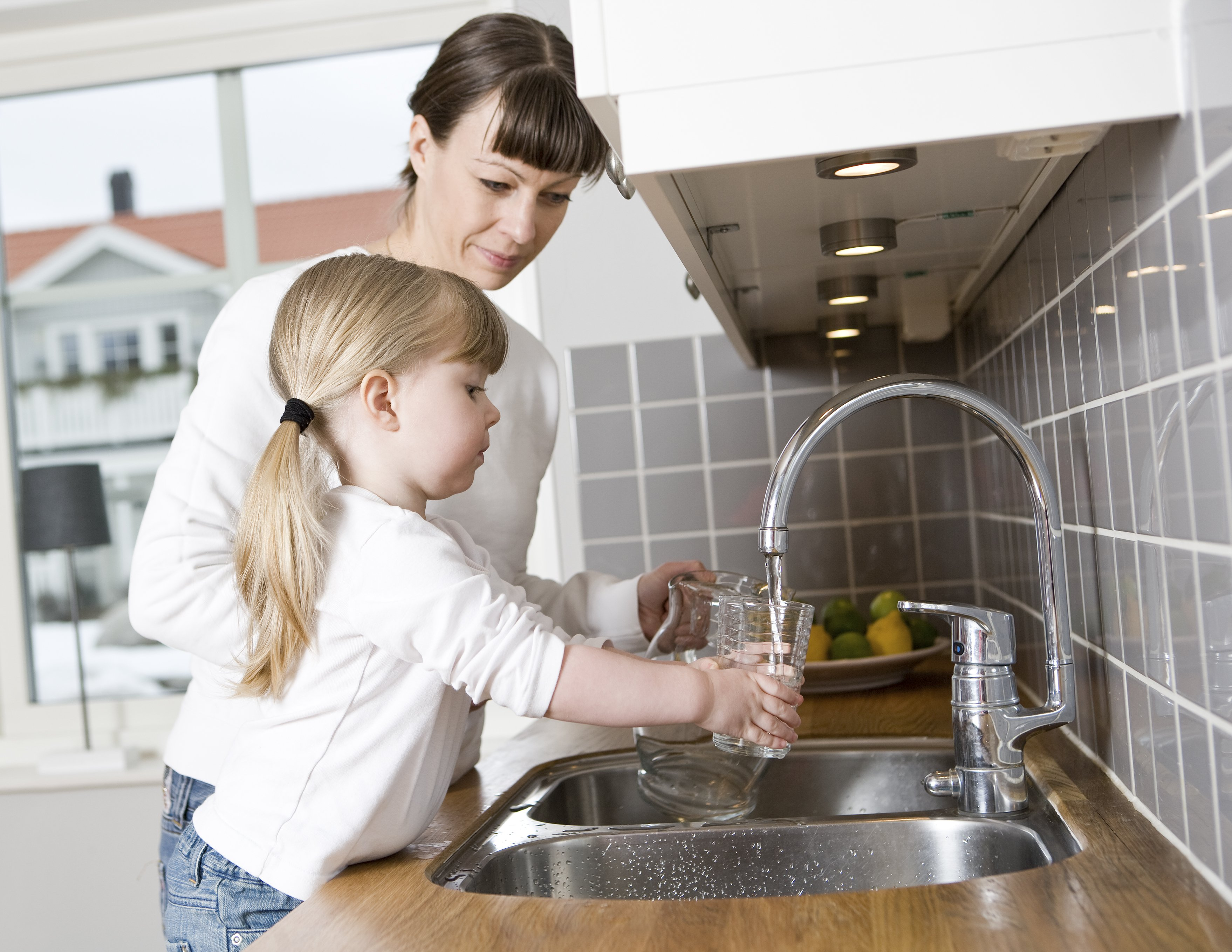 Girl and mother washing their hands in a sink